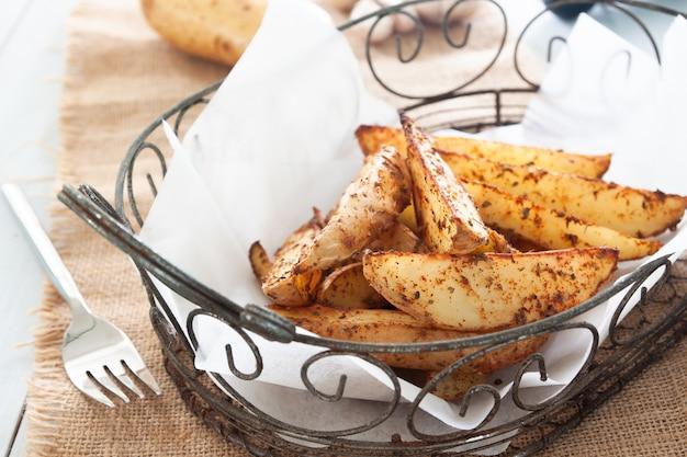 Ofenkartoffelkeile auf korb - selbst gemachtes organisches gemüse, kartoffel des strengen vegetariers zwängt snack-food-mahlzeit