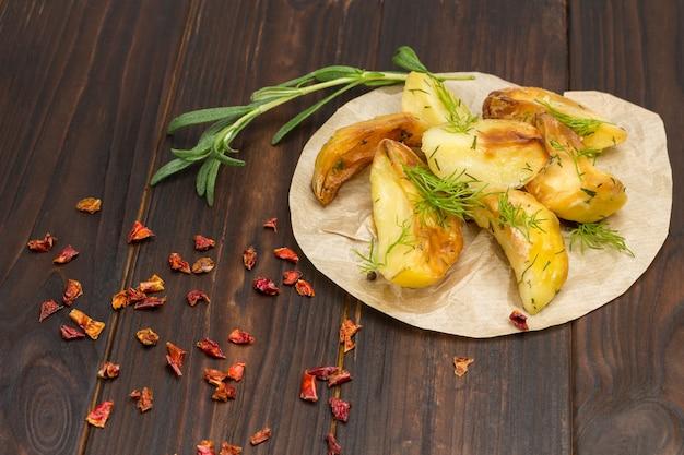 Ofenkartoffeln auf papier mit dill mit rosmarin und grünem paprika, knoblauch und zitrone
