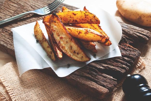 Ofenkartoffeln gedient auf rustikalem hölzernem brett. veganes essen oder snack. gesundes essen