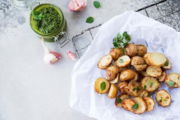Ofenkartoffeln im rustikalen stil mit grüner pesto-sauce