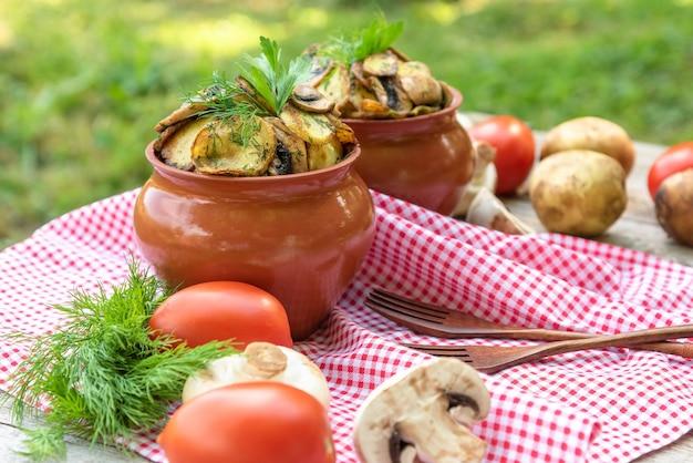 Ofenkartoffeln mit hühnchen und pilzen mit verschiedenen gewürzen. in tontöpfen