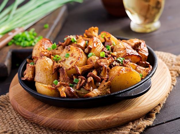 Ofenkartoffeln mit knoblauch, kräutern und gebratenen pfifferlingen in einer gusseisenbratpfanne.