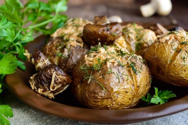 Ofenkartoffeln mit pilzen, käse und kräutern auf dunklem holz. nahansicht.