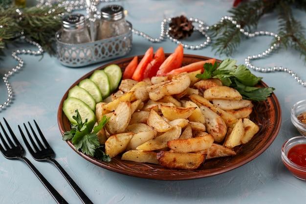 Ofenkartoffeln serviert mit tomaten, gurken und petersilie auf einem hellblauen teller