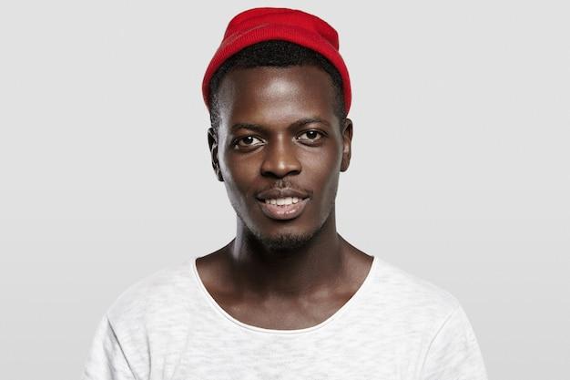 Offen und kontaktfreudig. hübscher glücklicher junger afroamerikanischer hipster, der roten trendigen hut trägt, lächelt und seine weißen zähne zeigt.
