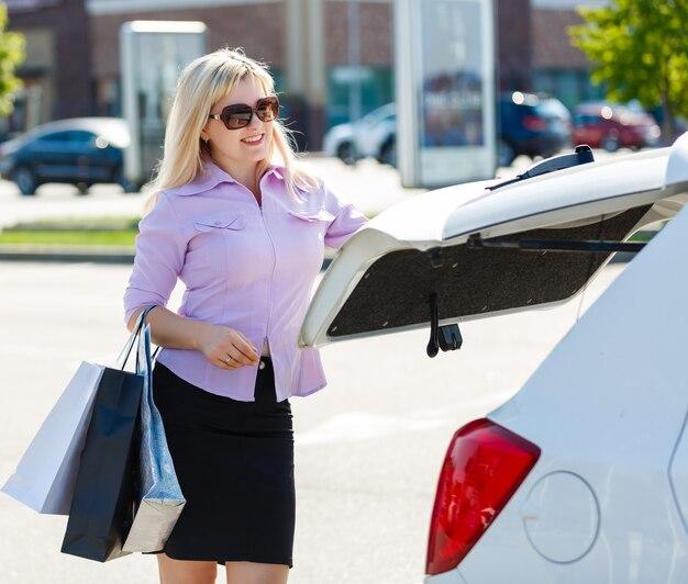 Offene autotür der jungen schönheit nach dem einkauf