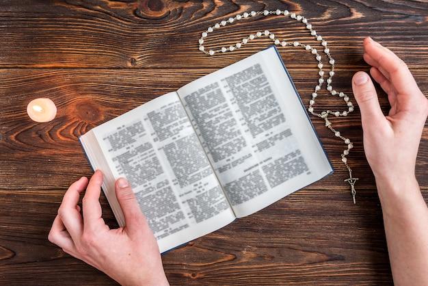 Offene bibel, kerze, christliches kreuz und menschliche hände auf holz