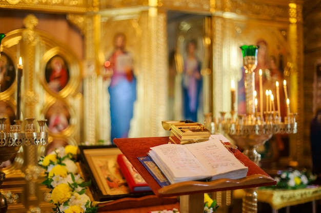 Offene bibel liegt auf dem altar am königstor in der kirche. die kiste mit dingen zur salbung des kindes während der taufe der orthodoxen kirche. weicher fokus