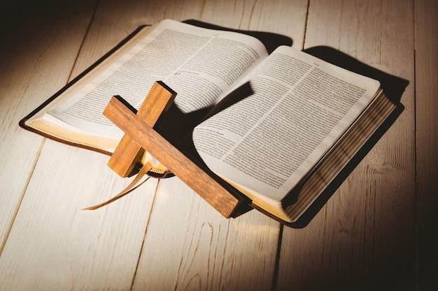 Offene bibel und holzkreuz