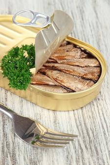 Offene blechdose mit sardinen auf hölzernem hintergrund