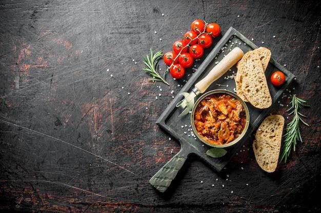 Offene blechdose mit sprotte in tomatensauce auf schneidebrett auf dunklem rustikalem tisch