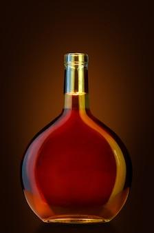 Offene cognac-flasche ohne etiketten auf dunkel