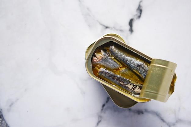 Offene dose sardinen auf weißem fliesenhintergrund