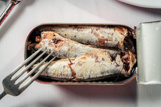 Offene dose sardinen in öl neben einer gabel auf einer weißen marmorähnlichen oberfläche. meeresnahrungsmittel