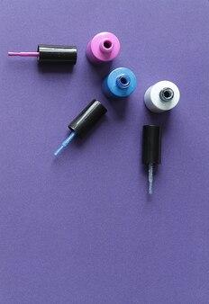 Offene flaschen nagellack auf lila hintergrund hautnah