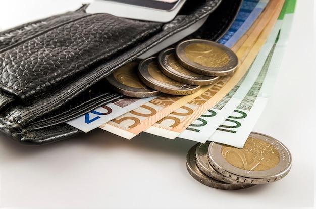 Offene geldbörse der ledernen männer mit den eurobanknotenrechnungen, münzen und kreditkarteninnere lokalisiert auf weißem hintergrund.