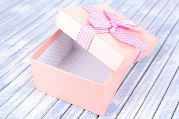 Offene geschenkbox auf holzuntergrund