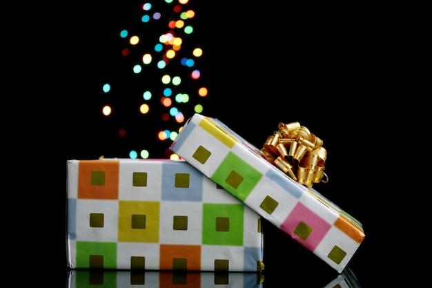 Offene geschenkbox mit bokeh-hintergrund auf schwarz