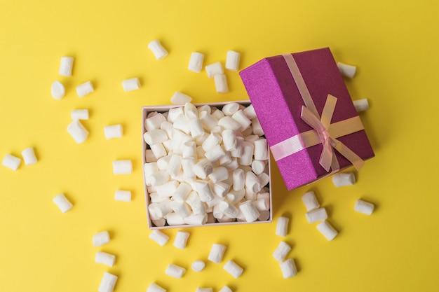 Offene geschenkbox mit vielen marshmallows auf gelbem hintergrund. ein süßer genuss. flach liegen.