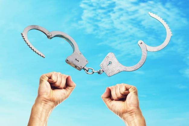Offene handschellen und hände erhoben sich inmitten des blauen himmels Premium Fotos