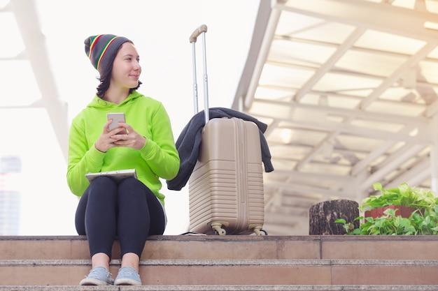 Offene karte des schönen mädchens schönes mädchen genießen reisendes lächeln. frauen sprechen über smartphones in der ci