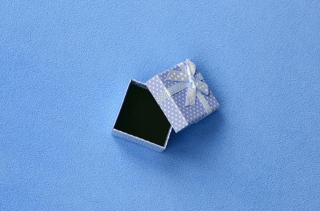 Offene kleine geschenkbox in blau mit einer kleinen schleife liegt auf einer decke