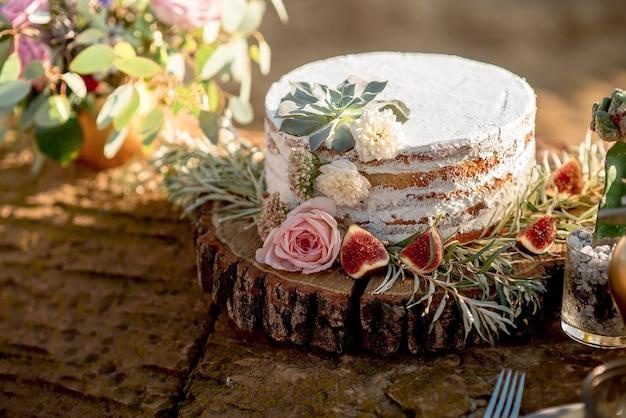 Offene kuchen-hochzeitstorte im rustikalen stil mit sahne-, feigen- und frischen blumendekorationen