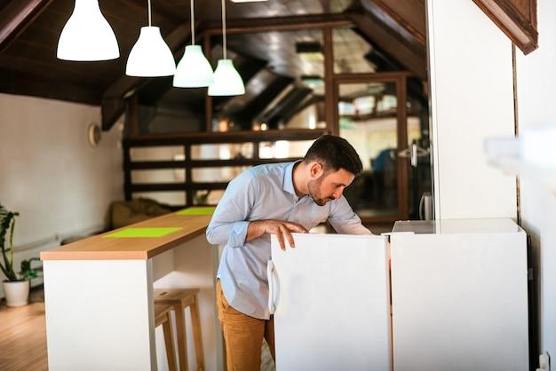 Offene kühlschranktür des mannes in der küche zu hause