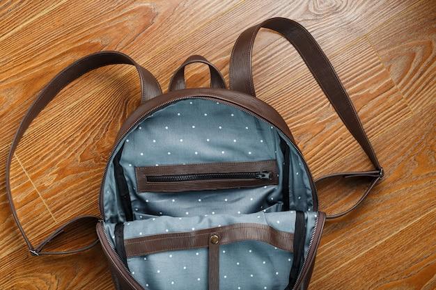 Offene leere tasche aus handgefertigtem echtleder mit elementen von schlössern auf einem holztisch.