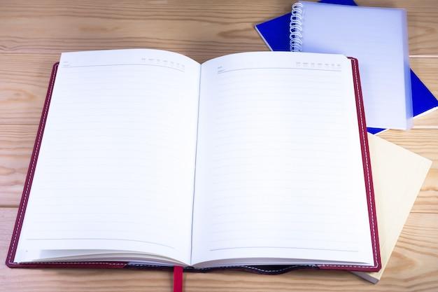 Offene notebooks auf hölzernen schreibtisch.