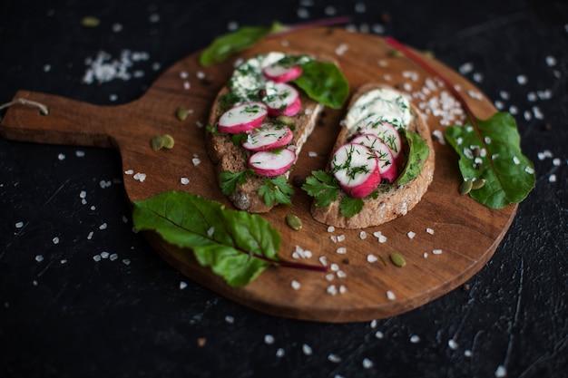 Offene sandwiches auf dunklem roggenbrot mit eiern, garnelen, radieschen, gurken und frischkäse