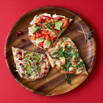 Offene sandwiches avocado und lachs, weichkäse. hausgemachtes sandwich mit garnelen und pilzen, mit hummus, auf holzbrett. draufsicht, sandwich nahaufnahme