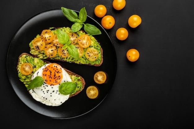 Offene sandwiches mit avocado-guacamole, gelben kirschtomaten, spiegelei und basilikum auf einem schwarzen teller. draufsicht. speicherplatz kopieren.