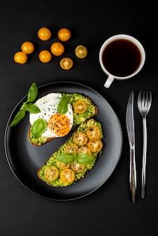 Offene sandwiches mit avocado-guacamole, gelben kirschtomaten, spiegelei und basilikum auf einem schwarzen teller. draufsicht.