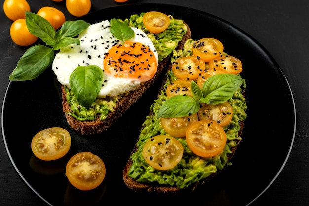 Offene sandwiches mit avocado-guacamole, gelben kirschtomaten, spiegelei und basilikum auf einem schwarzen teller. gesundes essen oder snack