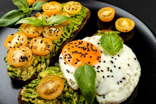 Offene sandwiches mit avocado-guacamole, gelben kirschtomaten, spiegelei und basilikum auf einem schwarzen teller. nahansicht.