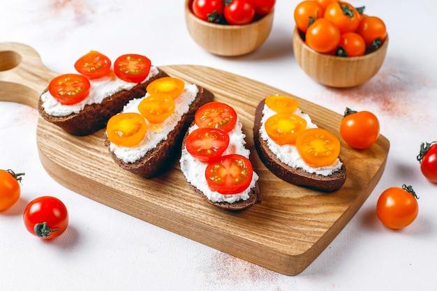 Offene sandwiches mit hüttenkäse, kirschtomaten und basilikum.