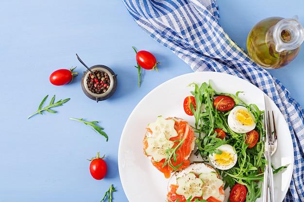 Offene sandwiches mit lachs-, frischkäse- und roggenbrot in einem weißen teller und salat