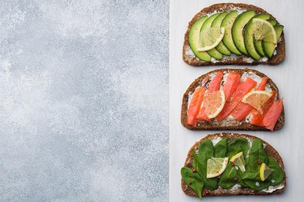 Offene sandwiches mit spinat- und avocadolachs auf einer grauen tabelle. platz kopieren