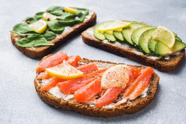 Offene sandwiches mit spinat- und avocadolachs auf einer grauen tabelle.