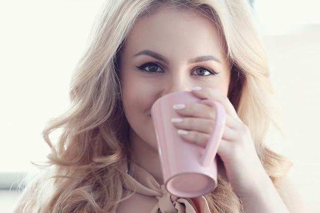 Offene schöne blonde frau, die tee oder kaffeetasse trinkt
