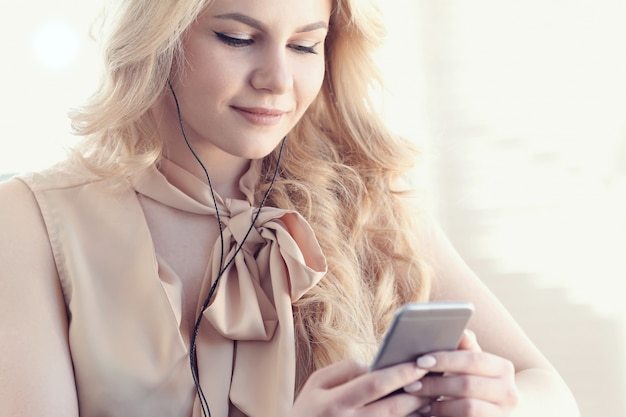 Offene schöne blonde frau mit smartphone