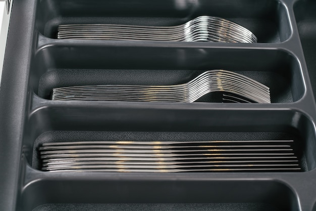 Offene schublade des küchenschranks mit schwarzem besteck-organizer-tablett mit gabeln, löffeln, messern. lagerorganisationssystem