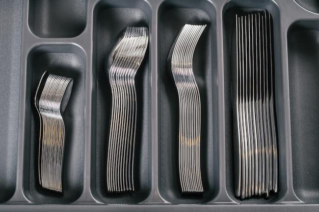 Offene schublade des küchenschranks mit schwarzem besteck-organizer-tablett mit silbernen gabeln, löffeln und messern. ordnungssystem für die küchenaufbewahrung. ansicht von oben