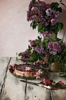 Offene torte mit beerengelee und beeren auf einem vintage-teller. stillleben mit fliederzweigen