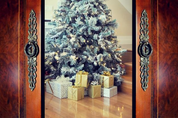 Offene tür und weihnachtsbaum im zimmer