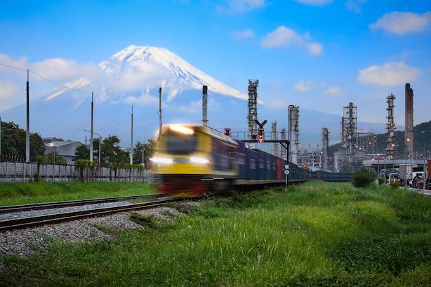 Offener beleuchtungsbewegungsvordergrund des raffinerieöl- und erdölindustrie-fabrikzonen- und -behälterfrachtlogistikzugtransports mit fuji-berg und blauem himmel