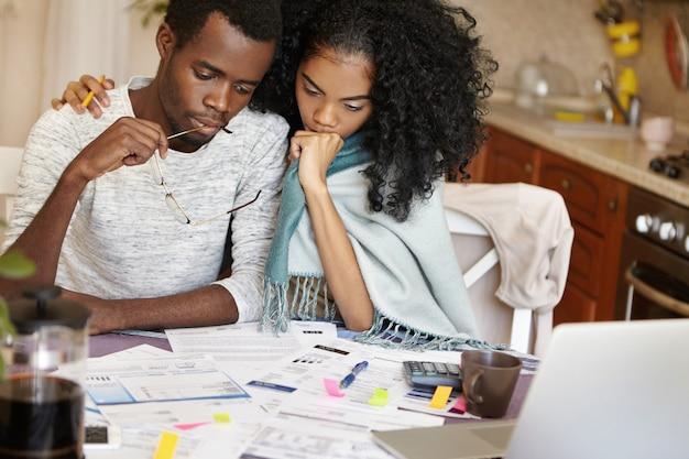 Offener innenschuss des afrikanischen mannes und der afrikanischen frau, die ausgaben zusammen berechnen