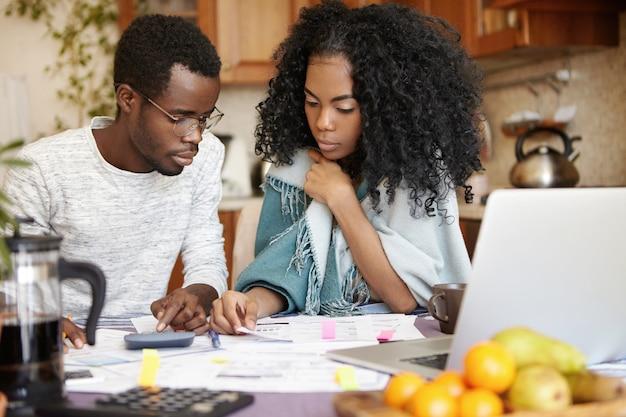 Offener innenschuss des jungen afroamerikanischen paares, das papierkram zusammen macht