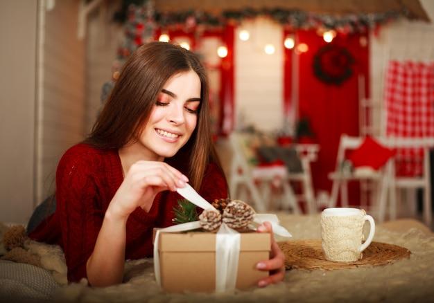 Offener kasten der frau mit geschenk auf szene von weihnachtsdekorationen